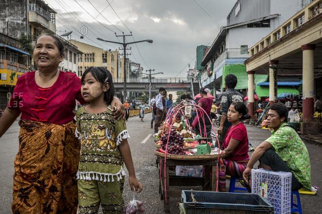 Yangon, Myanmar - 18 September 2016: People passing by a street food stand in downtown Yangon, Myanmar