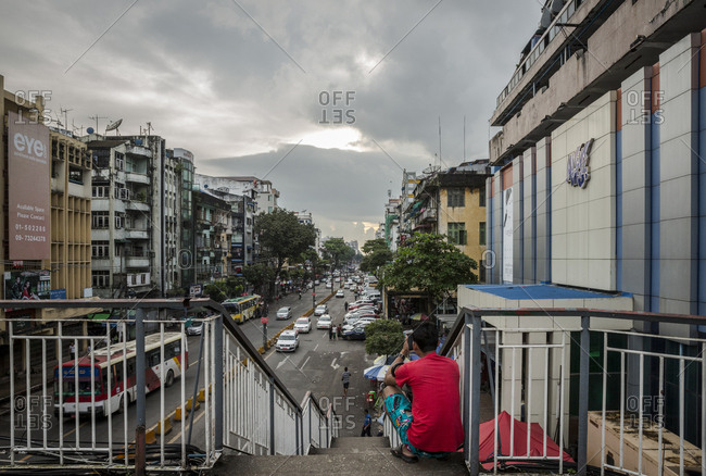 Yangon, Myanmar - 18 September 2016: Man sitting on a stairs above a Yangon street, Myanmar