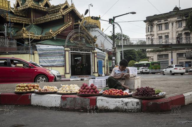 Yangon, Myanmar - 18 September 2016: Street fruit seller in a roundabout of downtown Yangon near Sule Pagoda, Myanmar