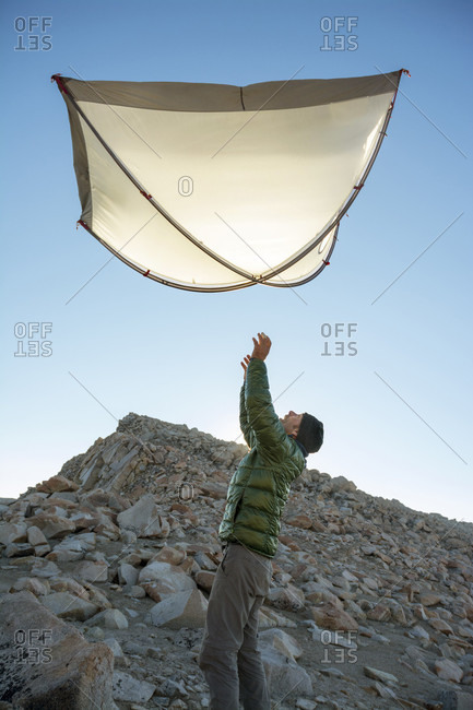 A man tossing his tent into the air while camping on Mount Fiske, Evolution Traverse, John Muir Wilderness, Kings Canyon National Park, Bishop, California