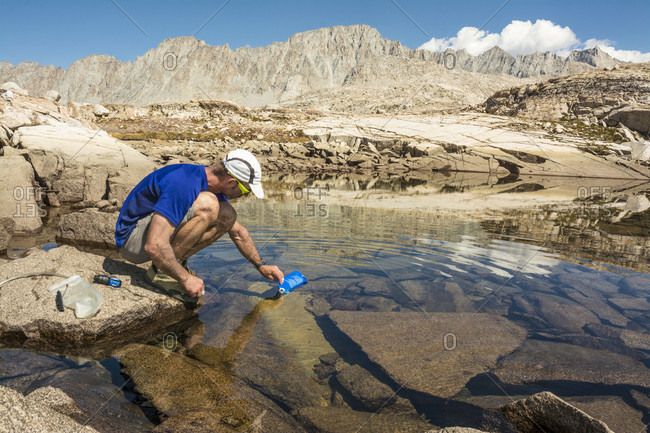 A man filtering water from the Evolution Basin Tarn, Evolution Traverse, John Muir Wilderness, Kings Canyon National Park, Bishop, California