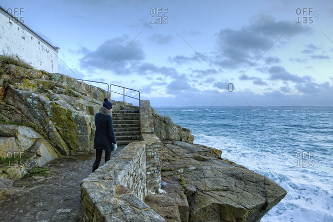 A woman watches a winter storm on a rocky headland, locality Le Courgant, in front of the Ile de Groix