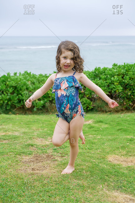 Three Year Old Girl Posing For The Camera In A Lifestyle Portrait Before Swimming At