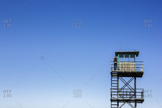 Hiking girl in Sutjeska national park in Bosnia and Herzegovina, looking over from a watch tower. Sunny day and blue sky over the scene