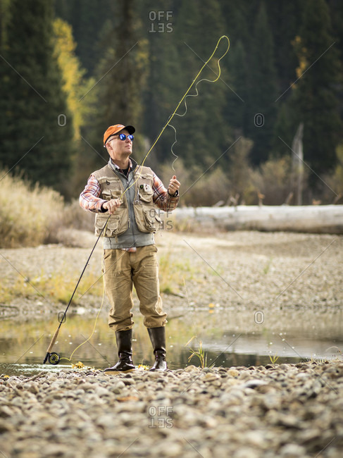 A man adjusts his fly rod while fishing near McCall, Idaho in the fall