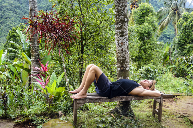 Man relaxing while lying on bench in tropical rainforest, Kintamani, Bali, Indonesia
