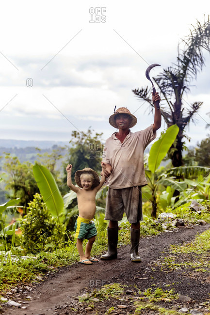 Indonesian farmer with sickle and boy standing while posing for picture, Kintamani, Bali, Indonesia