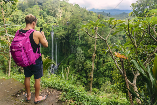 Man with backpack taking photo with smartphone in tropical rainforest, Kintamani
