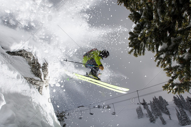 Climber, professional skier, bursts through powdered snow while jumping off of a cliff. Alta, Utah
