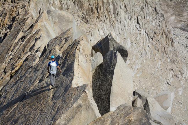 A man negotiating the granite ridgeline along the Evolution Traverse, John Muir Wilderness, Kings Canyon National Park, Bishop, California