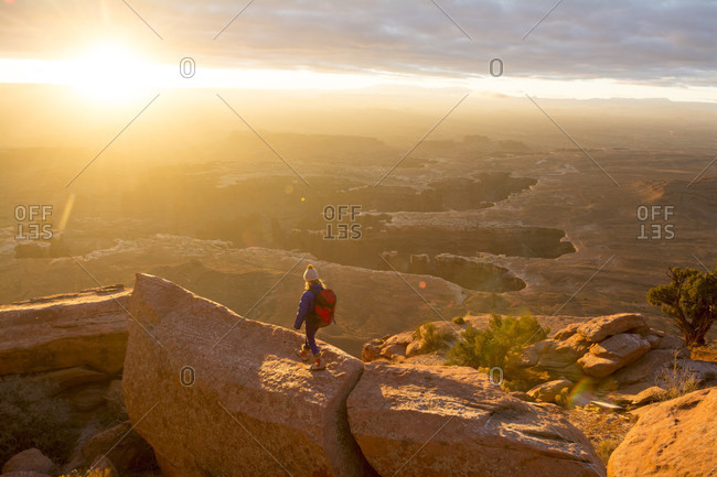 A young girl hiking on Grand View Point above Monument Basin, Island in the Sky, Canyonlands National Park, Moab, Utah