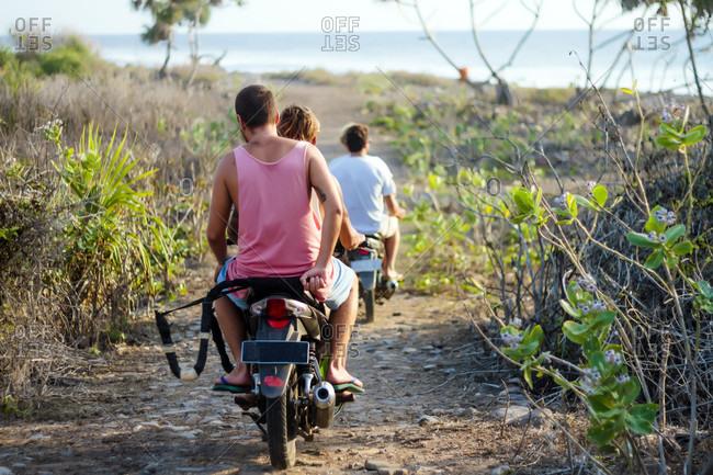 Friends traveling by motorbike along dirt road, Lakey Peak, Central Sumbawa, Indonesia