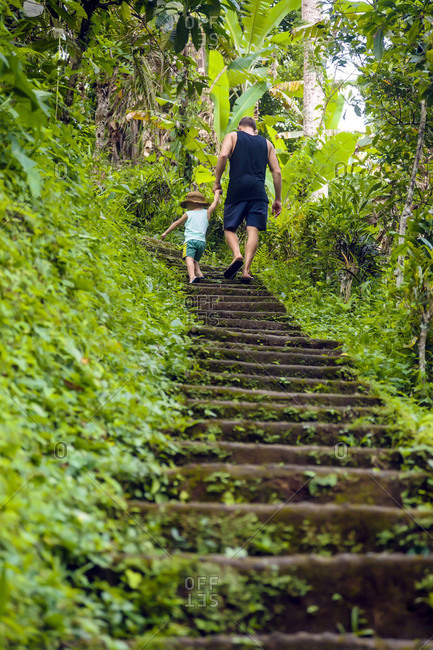 Father and son walking up steps while hiking in jungle, Kintamani, Bali, Indonesia