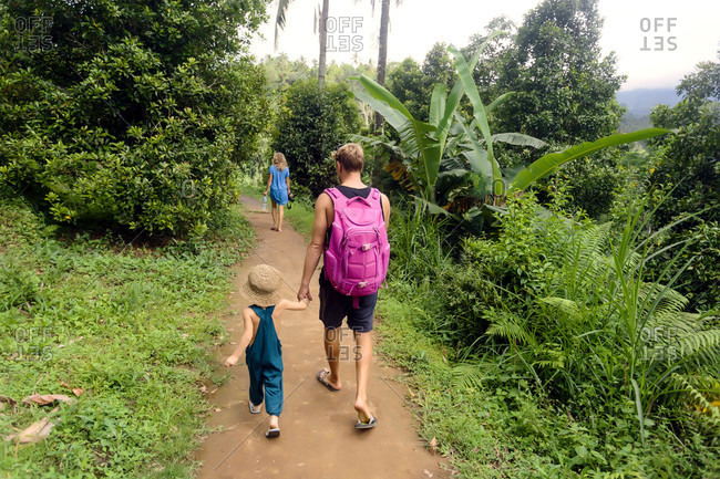 Family walking on footpath while hiking in jungle, Kintamani, Bali, Indonesia