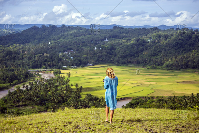 Tranquil scene of young woman wearing blue dress standing in mountains, Sumba, Indonesia
