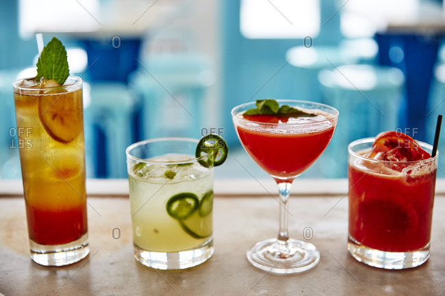 A lineup of four freshly poured colorful cocktails sit on a bar