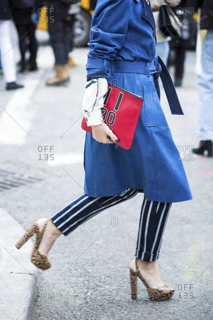 London, England 2016: Woman wearing blue trench coat and carrying red bag crossing street
