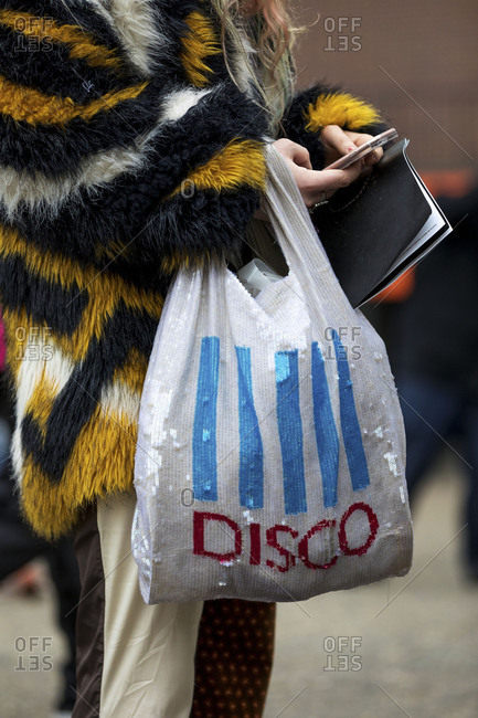 London, England 2017: Woman wearing fur coat carrying sequin bag