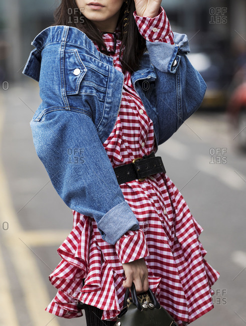 London, England 2017: Fashionable woman wearing red and white dress with a jean jacket