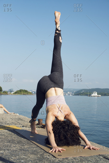 Oslo, Norway 2016: Woman doing yoga on the shore of Oslo, Norway