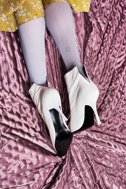 Paris, France 2017: Feet of a woman wearing white heels on shiny pink blanket