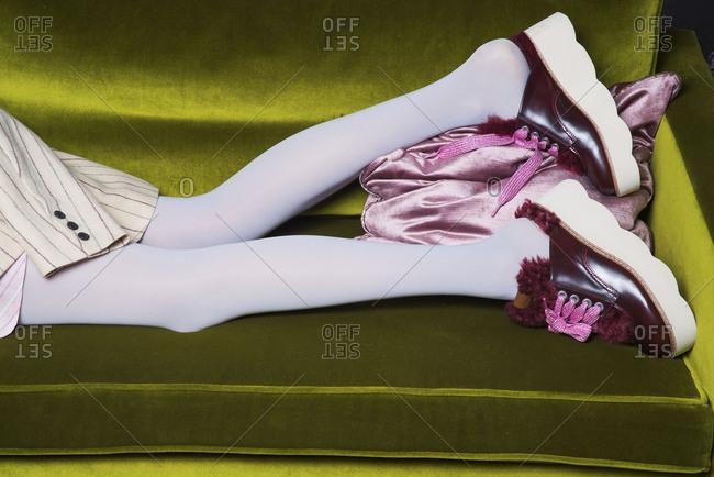 Paris, France 2017: Legs of a woman lying on a green velvet sofa