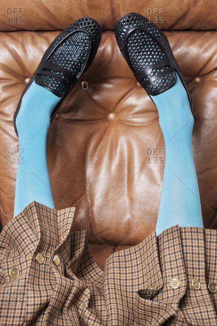 Paris, France 2017: Legs of a woman wearing blue tights on a leather sofa