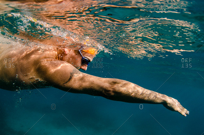British Virgin Islands - May 13, 2015: Profile of a man with a tattoo on his shoulder swimming at the surface of the ocean