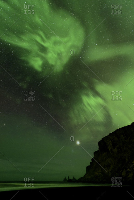 Green aurora in fine patterns and Jupiter above Atlantic Ocean coastline and basalt sea stacks in South Iceland