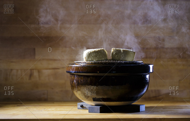 Smoked tofu rests on top of a donabe grill, a specialized form of Japanese cookware