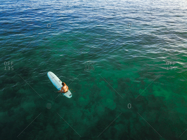 A surfer waits for waves in clear blue water