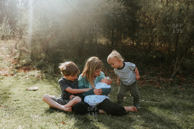 Children sitting with newborn sibling outdoors