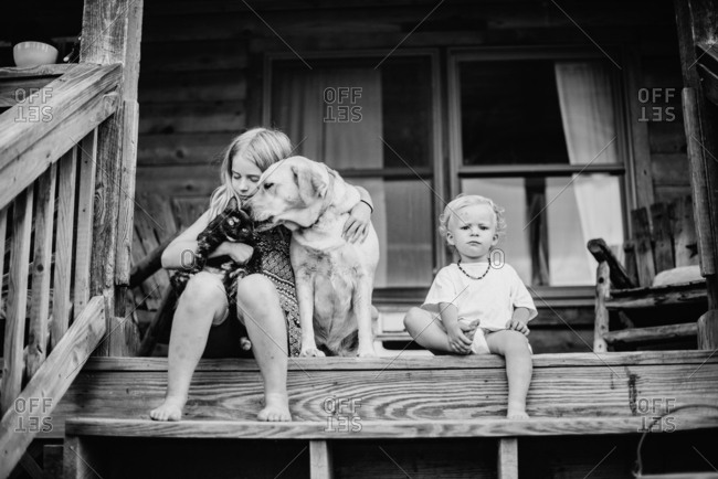 Kids sitting on front porch with cat and dog