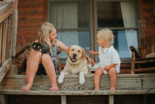Siblings sitting on front porch with cat and dog