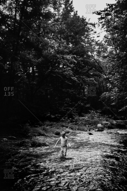 Boy swimming in a river in black and white
