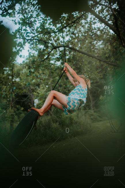 Girl swinging on a tire swing