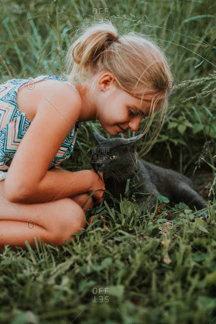 Cat licking young girl's hand
