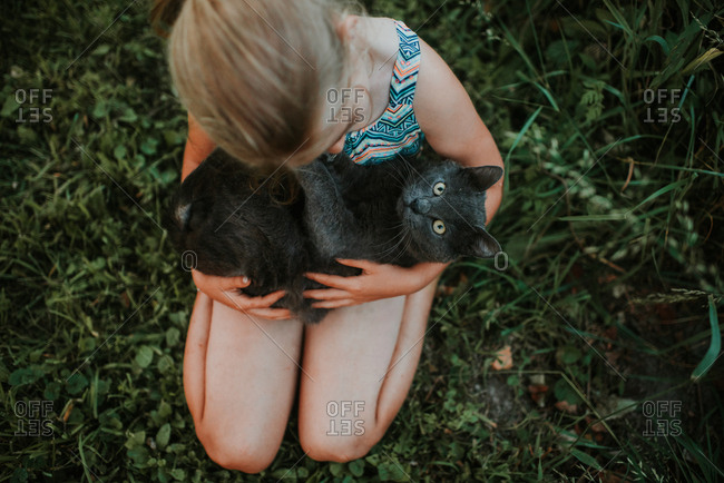 Overhead view of girl holding gray cat