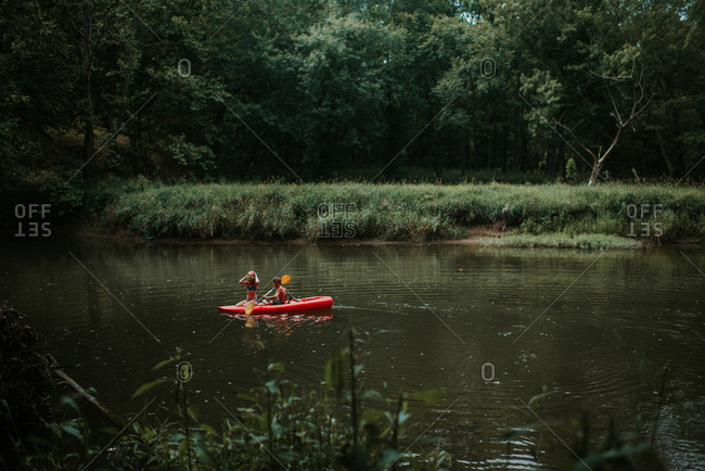Two siblings kayaking on a river