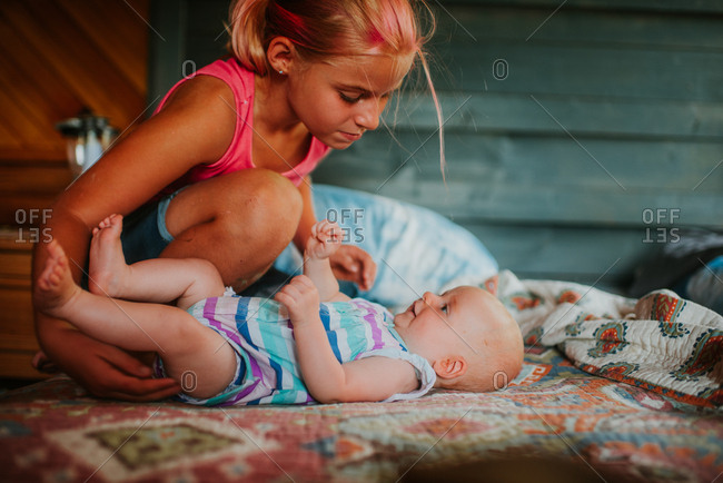 Girl looking at baby sister on a bed