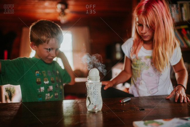 Siblings doing science experiment with smoke and egg