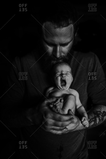 Father holding newborn yawing baby in black and white