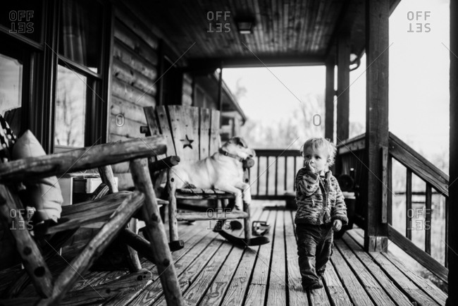 Toddler walking on a porch sucking thumb