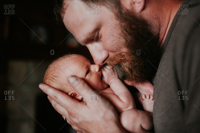 Father holding newborn baby and touching noses