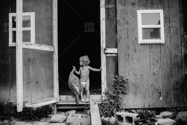 Toddler standing in barn door holding fake pheasant