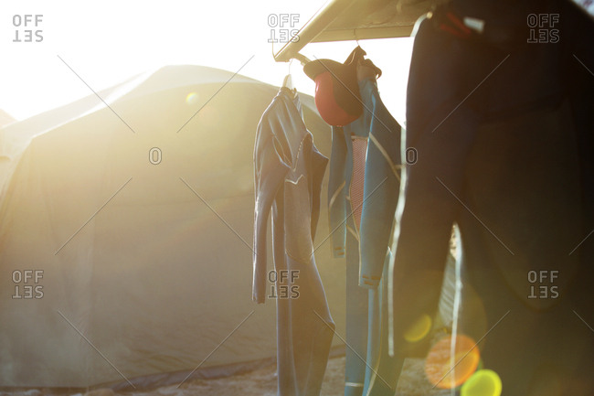 Wetsuits hanging against tent at beach on sunny day