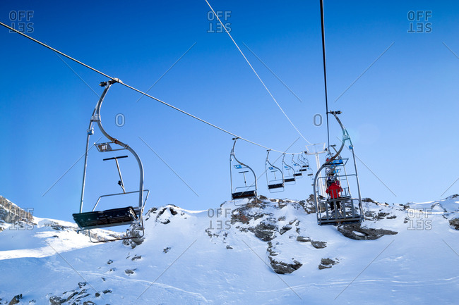 A chair lift carries skiers up a summit