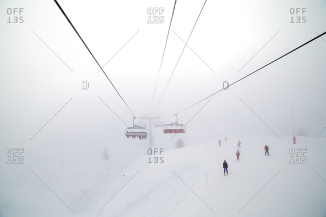 A ski lift carries skiers to a busy summit