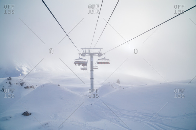A ski lift carries skiers up a misty mountain