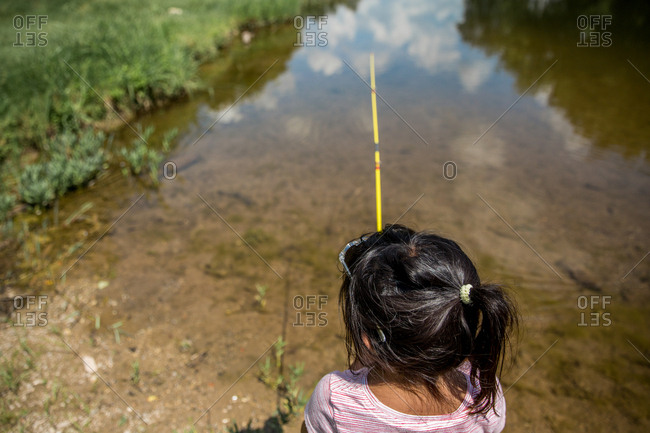 Back view of girl fishing in calm water